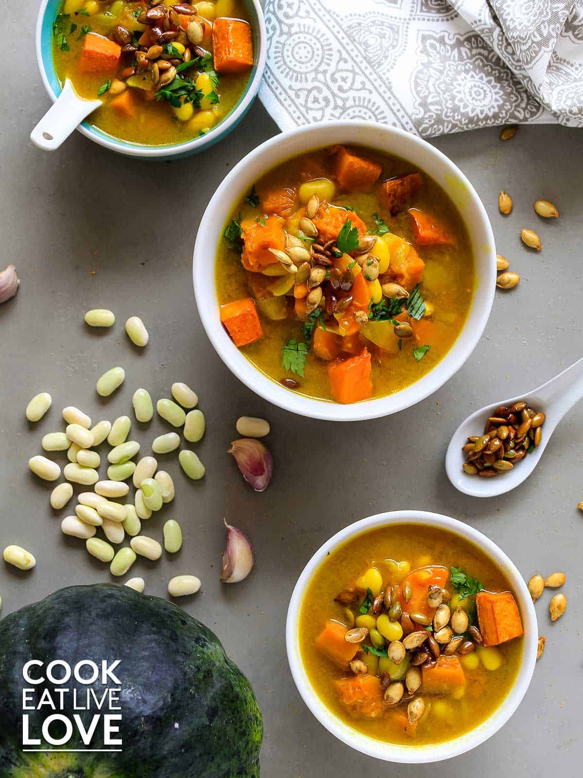 Three bowls of healthy pumpkin soup on gray background. White beans and toasted pumpkin seeds around the bowls.