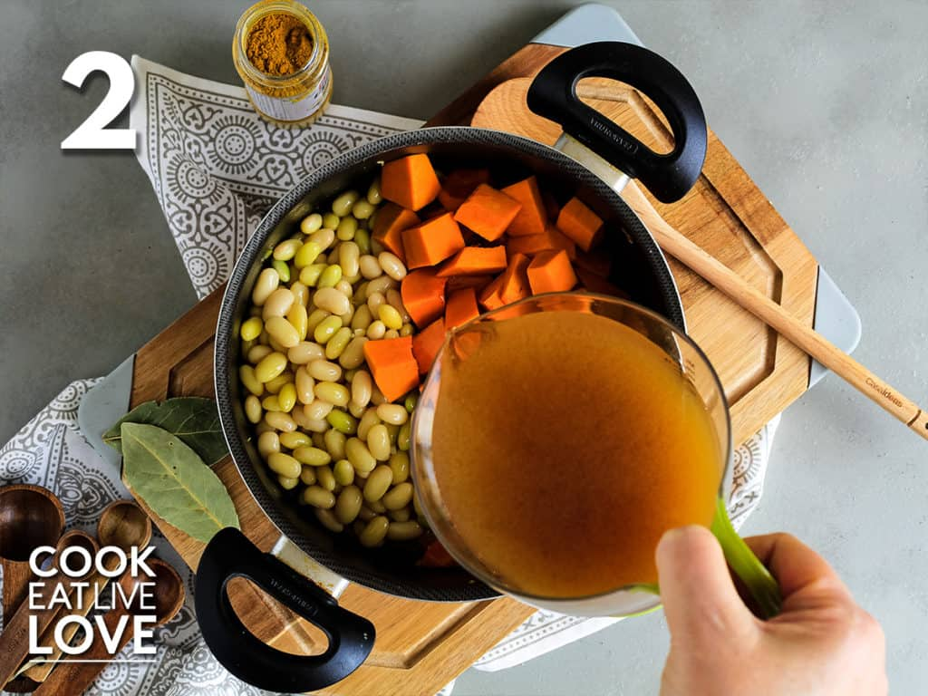 Pot with beans and pumpkin added and vegetable broth being poured into pot.