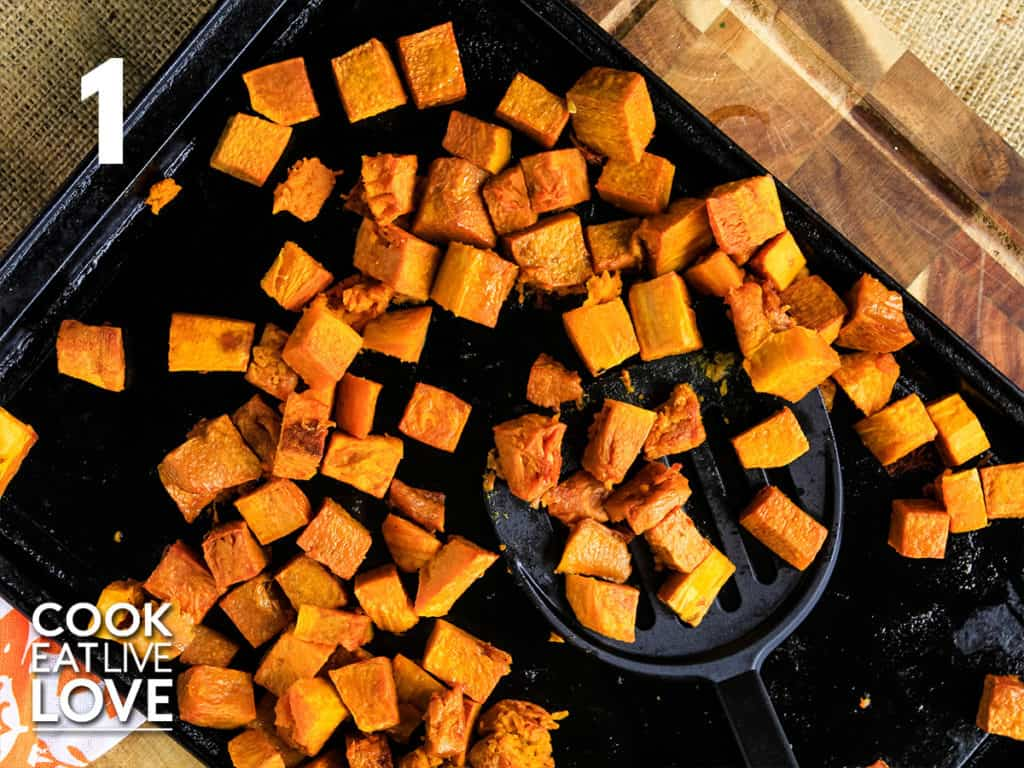 Overhead view of butternut squash roasting on a pan.