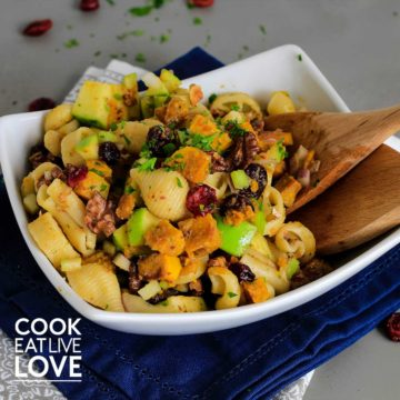 Fall pasta salad in white rectangle bowl with wooden serving spoons.