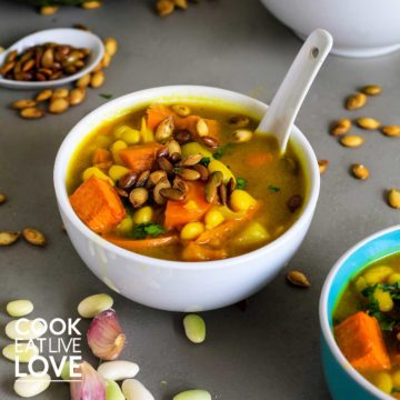 Bowl of healthy pumpkin soup with ceramic white spoon in bowl. Around the bowl are white beans and pumpkin seeds.