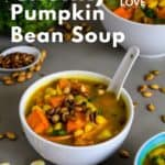 Pin for pinterest with front view of bowl of pumpkin soup with spoon in bowl.