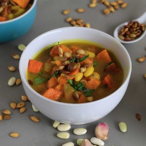 Healthy pumpkin soup served up in white bowl.