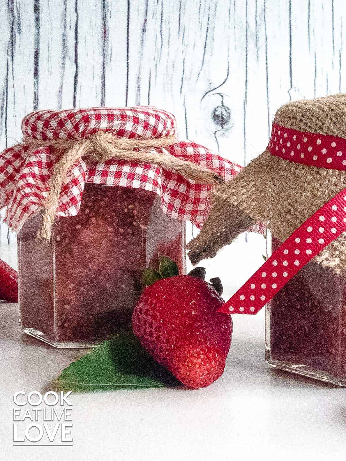 Strawberry jam with fresh berries in front make easy healthy homemade food gifts.