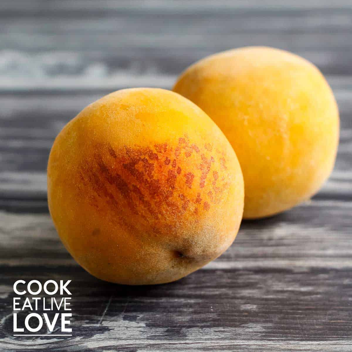 Whole peaches on gray wooden background.