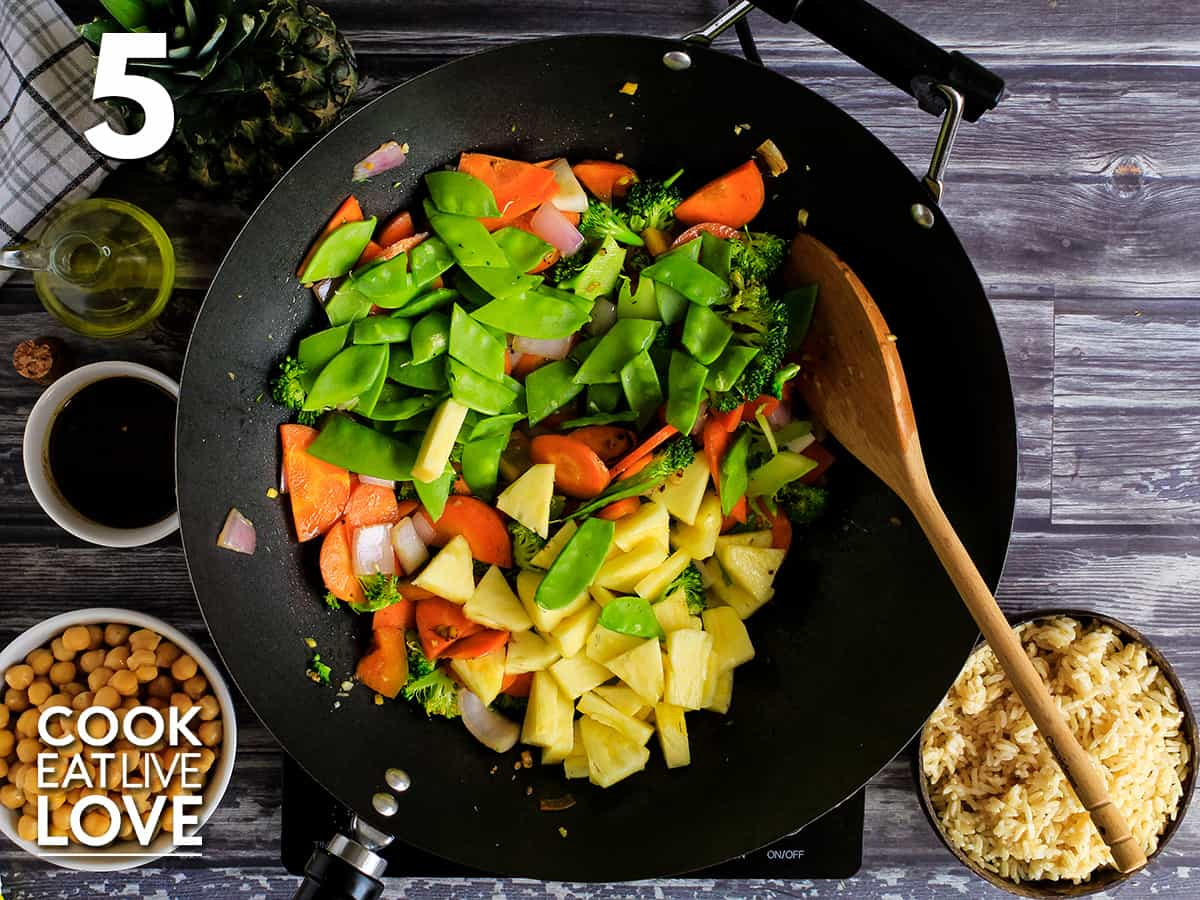 Pineapple and snow peas are added to the other cooked vegetables.