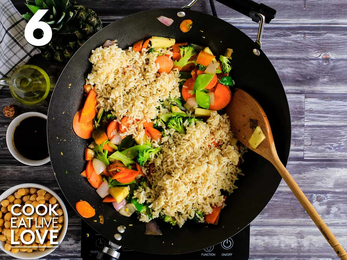 Rice is added to wok with cooked vegetables.