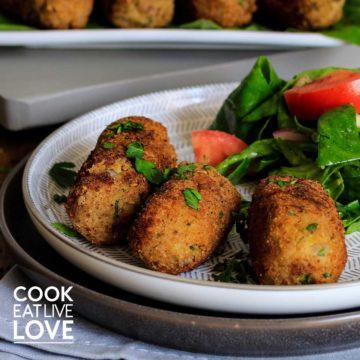 Potato quinoa croquettes on plate with salad.