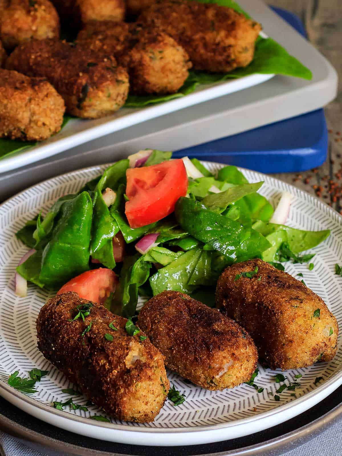 Front view of cooked potato quinoa croquettes on plate with small salad.