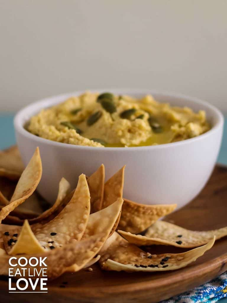 A bowl of hummus with chips in front