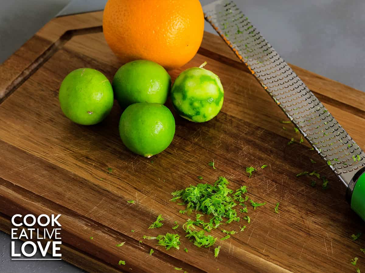 Limes and orange on cutting board with zested lime and microplane in background.