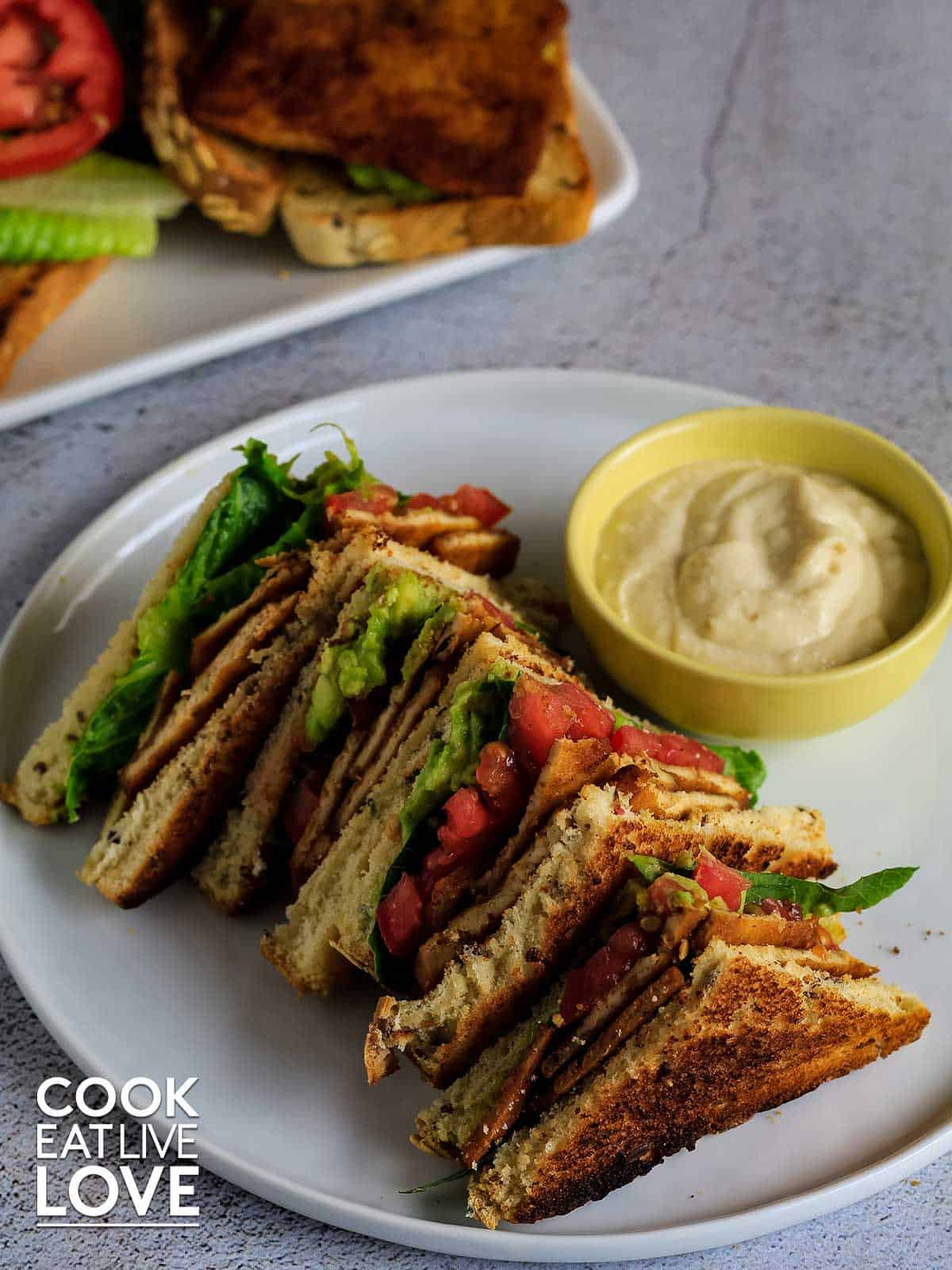 Vegan Blt ready to eat on a plate with creamy mayo sauce.
