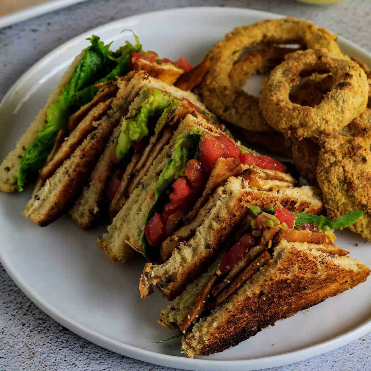 Vegan blt sandwich served up on white plate with onion rings.