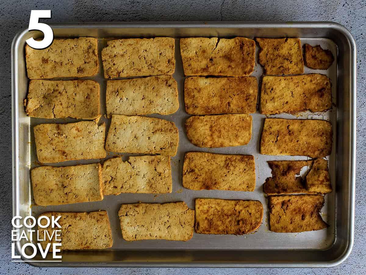 Tofu on pan, half of it flipped over on baking pan halfway through cooking time.