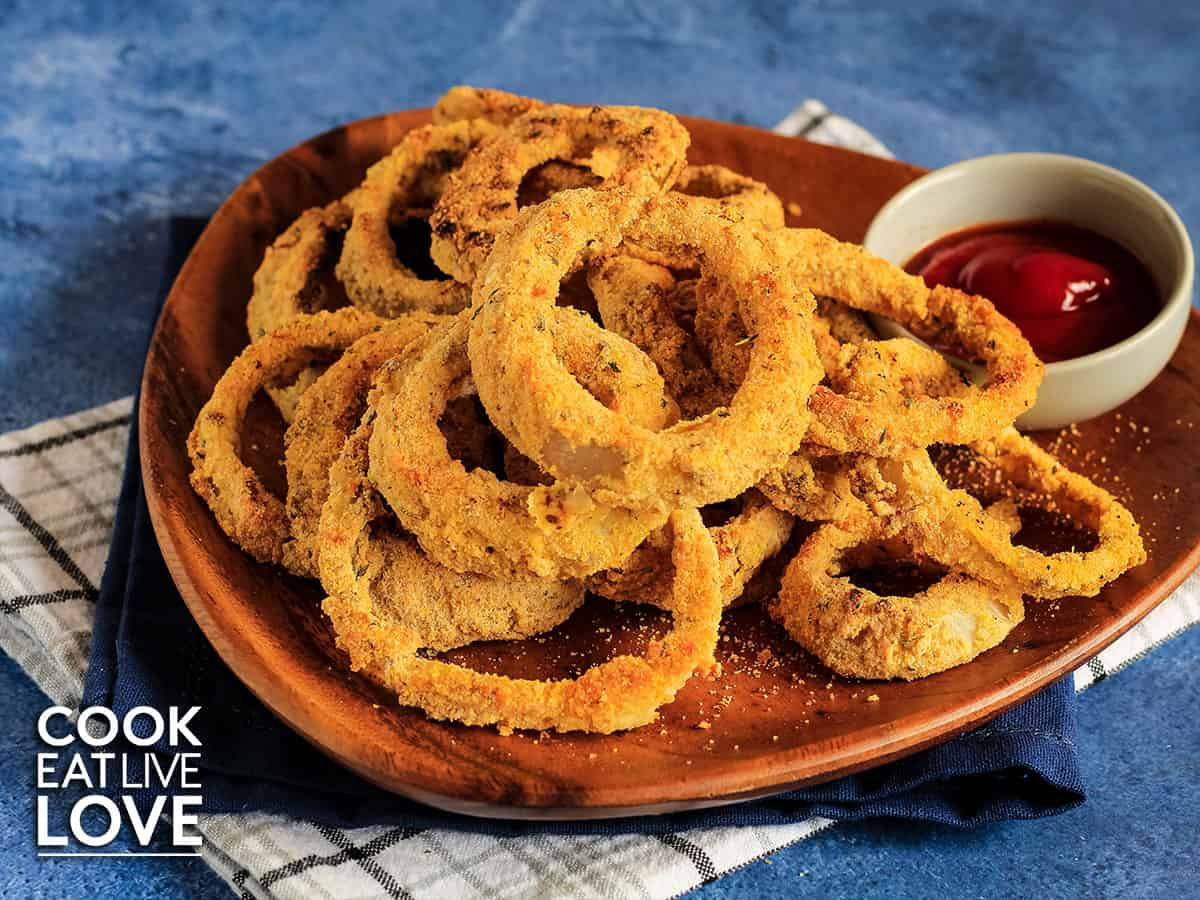 Plate of vegan baked onion rings with ketchup.