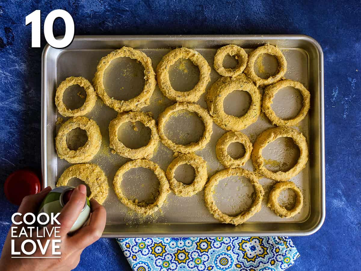 Onion rings finished breading process on a baking pan and ready for the oven.