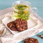 Two chocolate oatmeal cookies on rectangle plate with chamomile tea in glass mug.