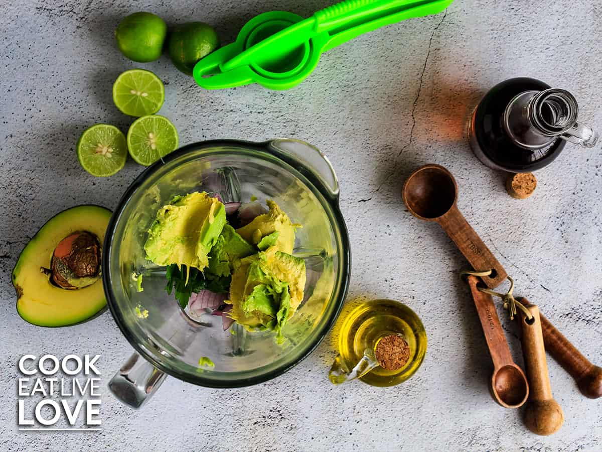 All the ingredients in a blender to make this easy avocado sauce recipe.