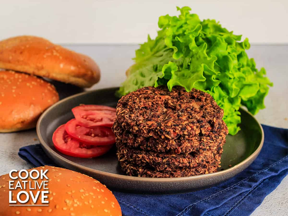 Stack of black bean quinoa burgers on a plate with leaf lettuce and tomato slices.