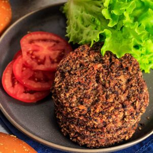 Close up from overhead of stack of black bean quinoa burgers.