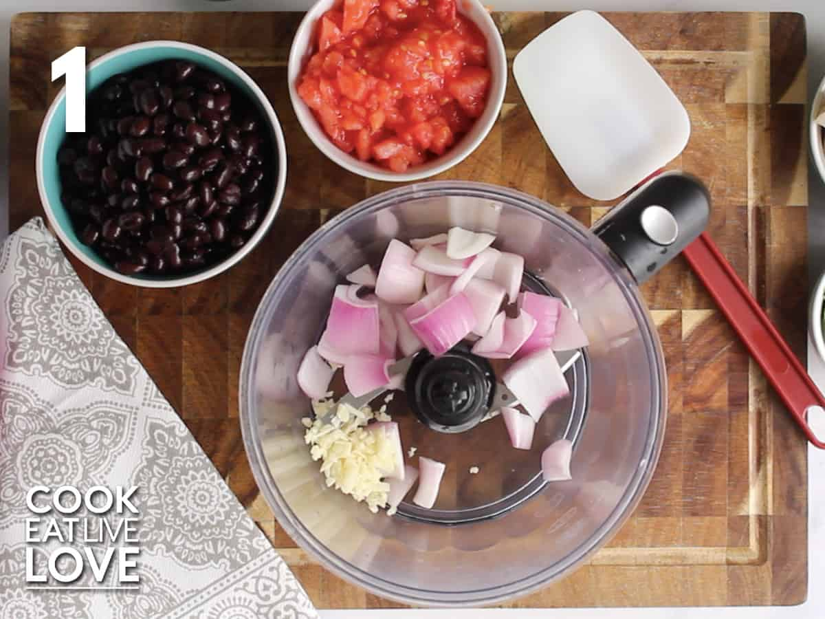 Food processor with red onions and garlic to start making black bean quinoa burgers.
