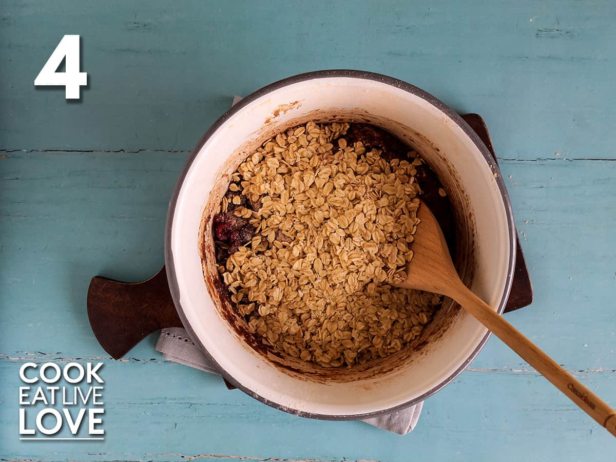 Oats, chips and dried cranberries are added and stirred with spoon to mix.