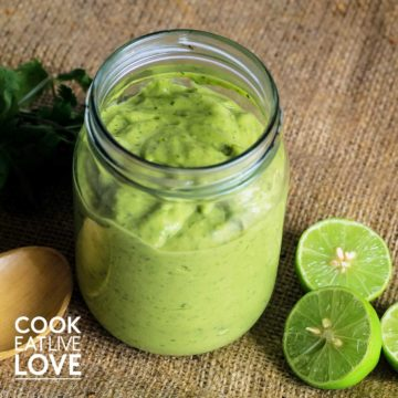 Jar on creamy avocado sauce with limes and parsley on burlap.