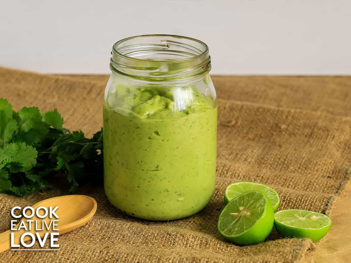 Jar of creamy avocado sauce on burlap with spoon and cut limes to the side.