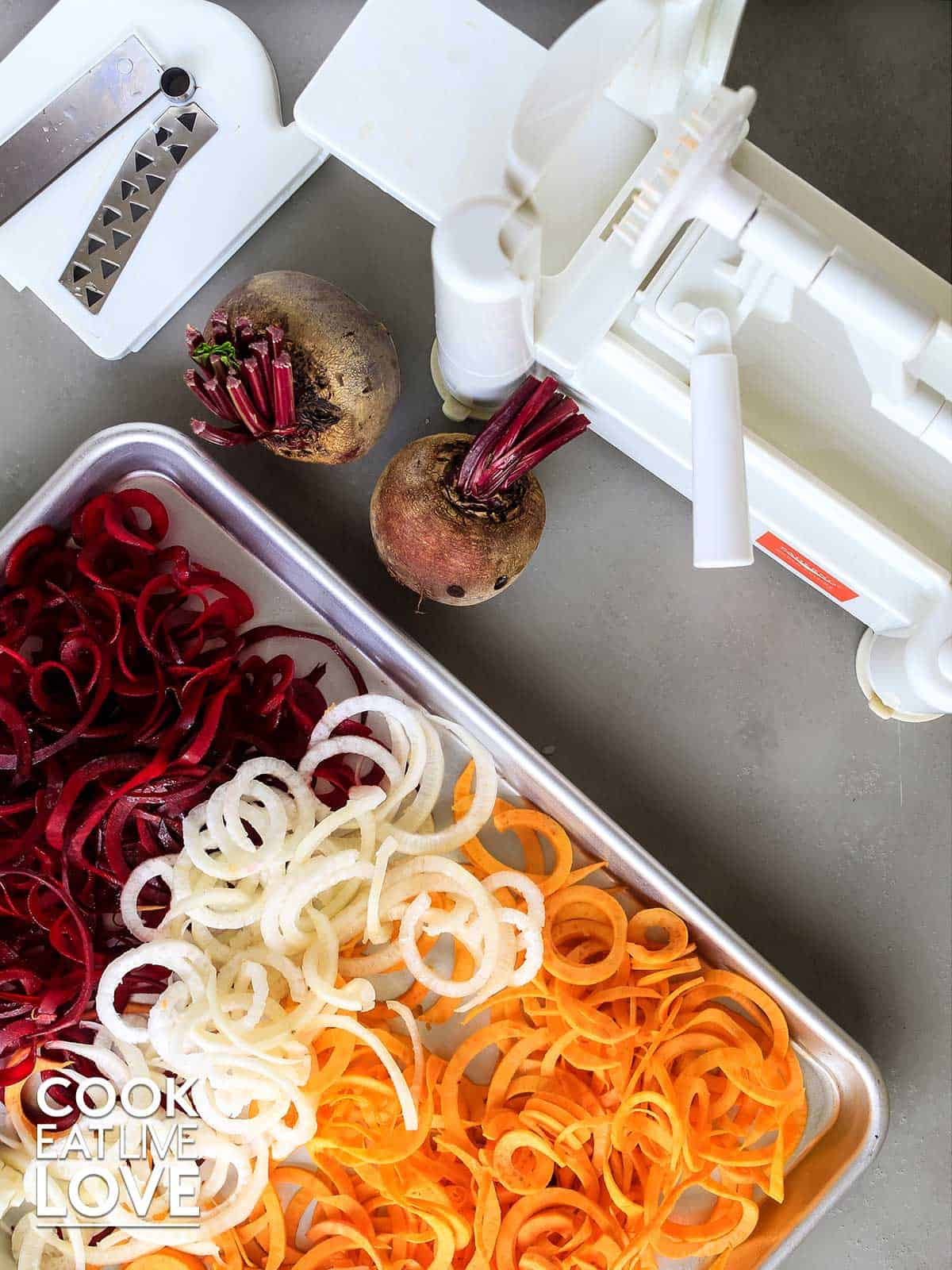 Spiralized veggies on a baking pan with spiralizer at top of picture.