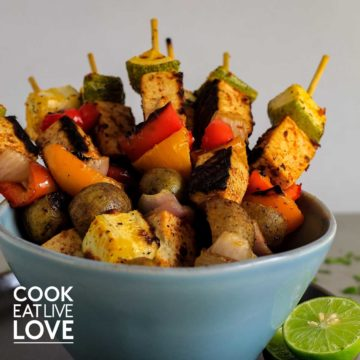 A bowl of tofu and veggies on skewers