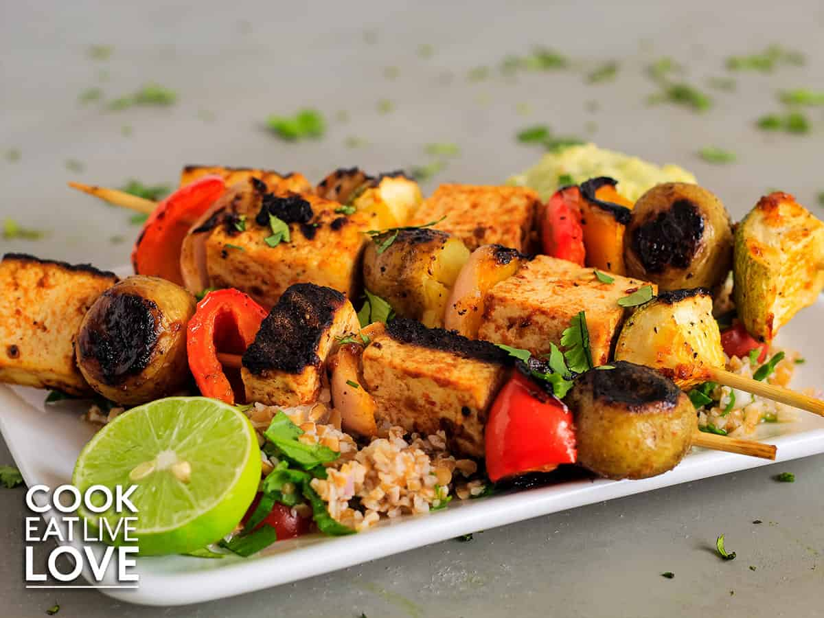 Closeup of grilled tofu skewers on a white plate served over bulgur pilaf with lime.