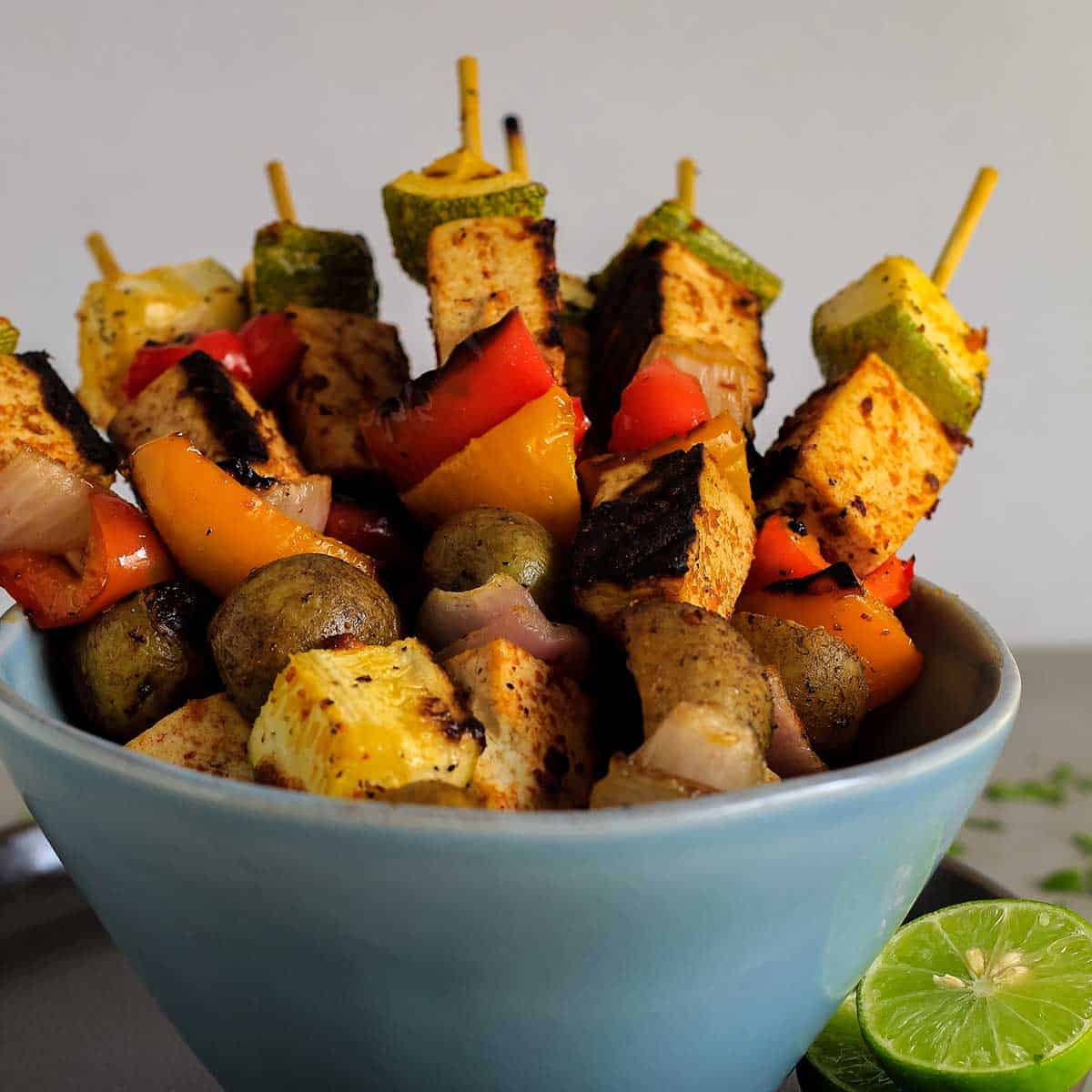 Bowl of tofu skewers with skewers standing up in bowl for serving.
