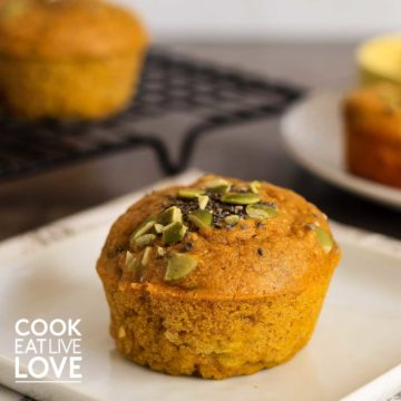Closeup view of pumpkin zucchini muffin on white plate with more muffins in background.