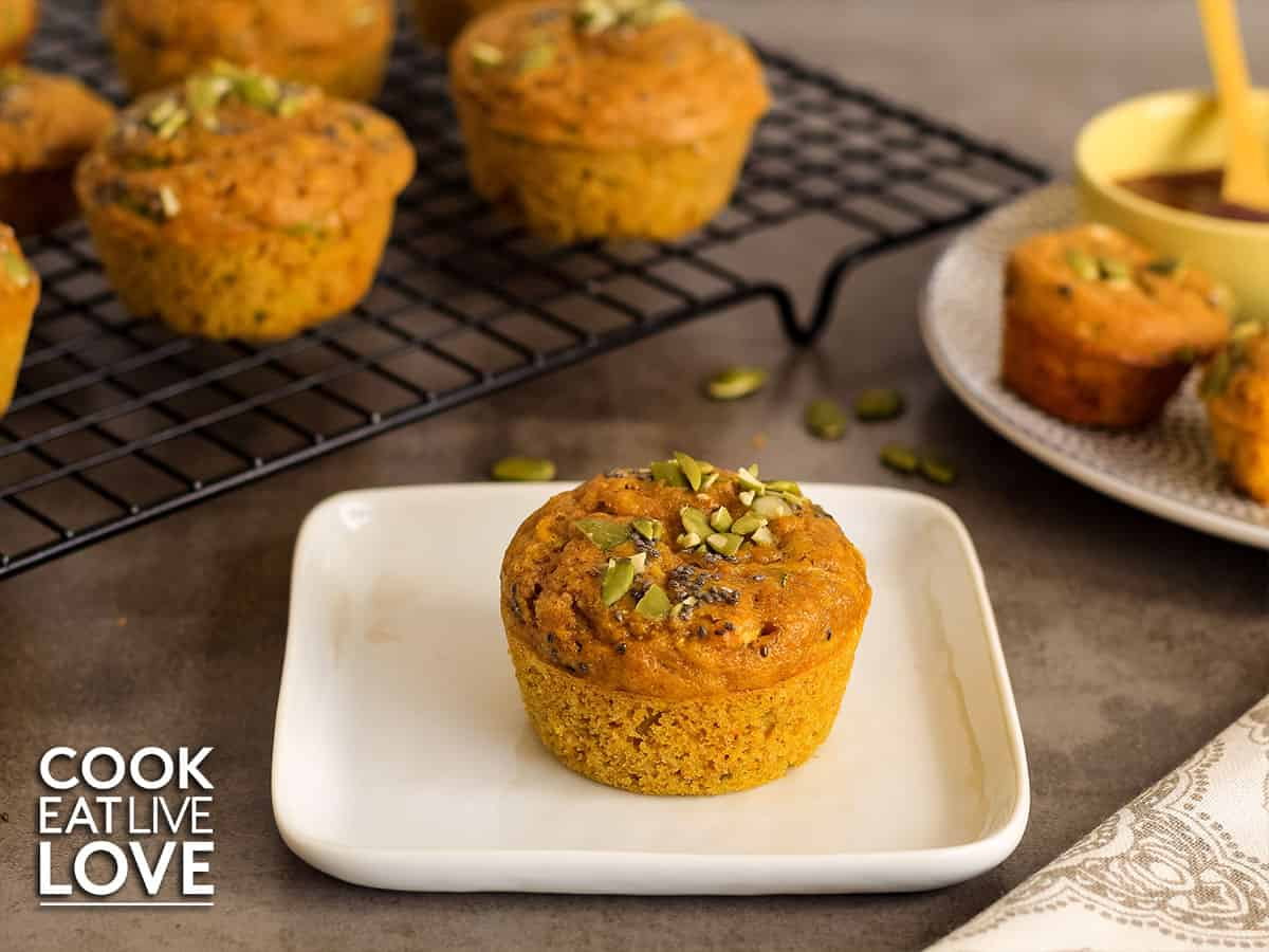 Closeup view of single pumpkin zucchini muffin on white plate with more on cooling rack and plate.
