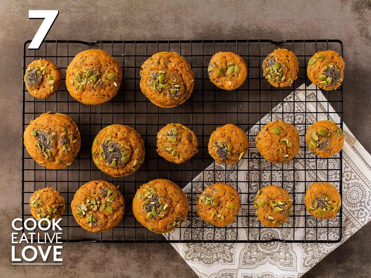 Pumpkin zucchini muffins fresh from the oven are on a cooling rack.