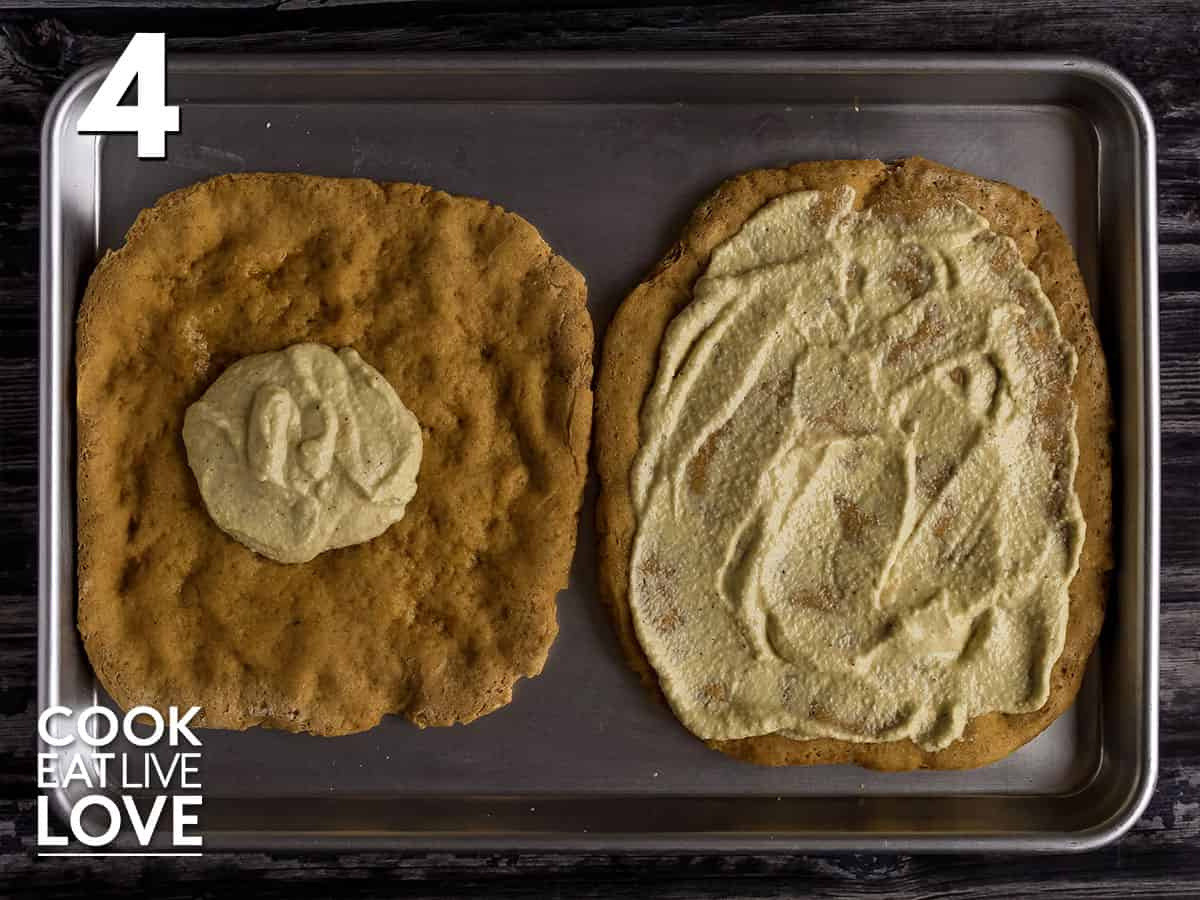 Pizza crust on baking sheet topped with vegan alfredo sauce, the base for vegan white pizza.
