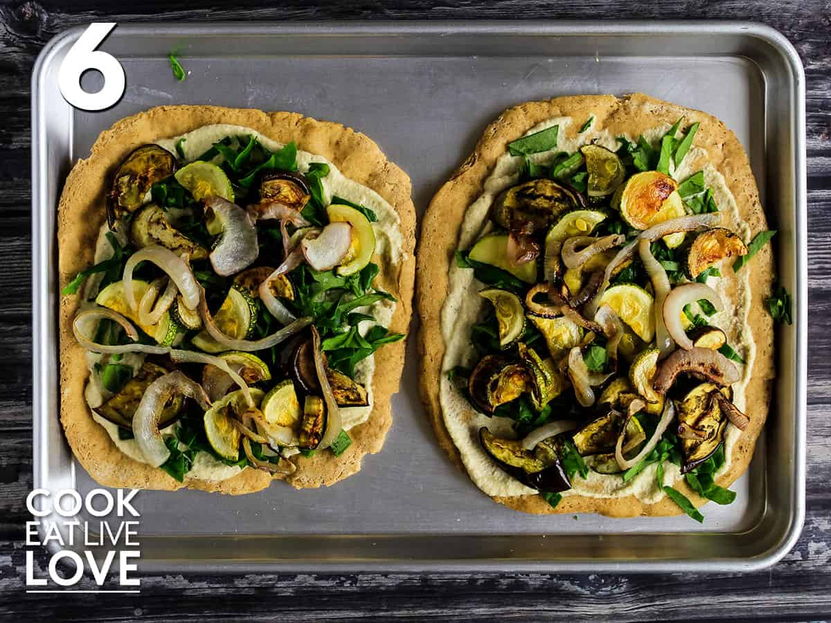 Two pizza crusts for vegan white pizza topped with roasted vegetables.