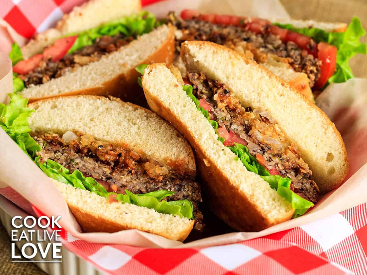 Vegetarian bbq burgers cut in half and served up in red and white checkered lined basket.