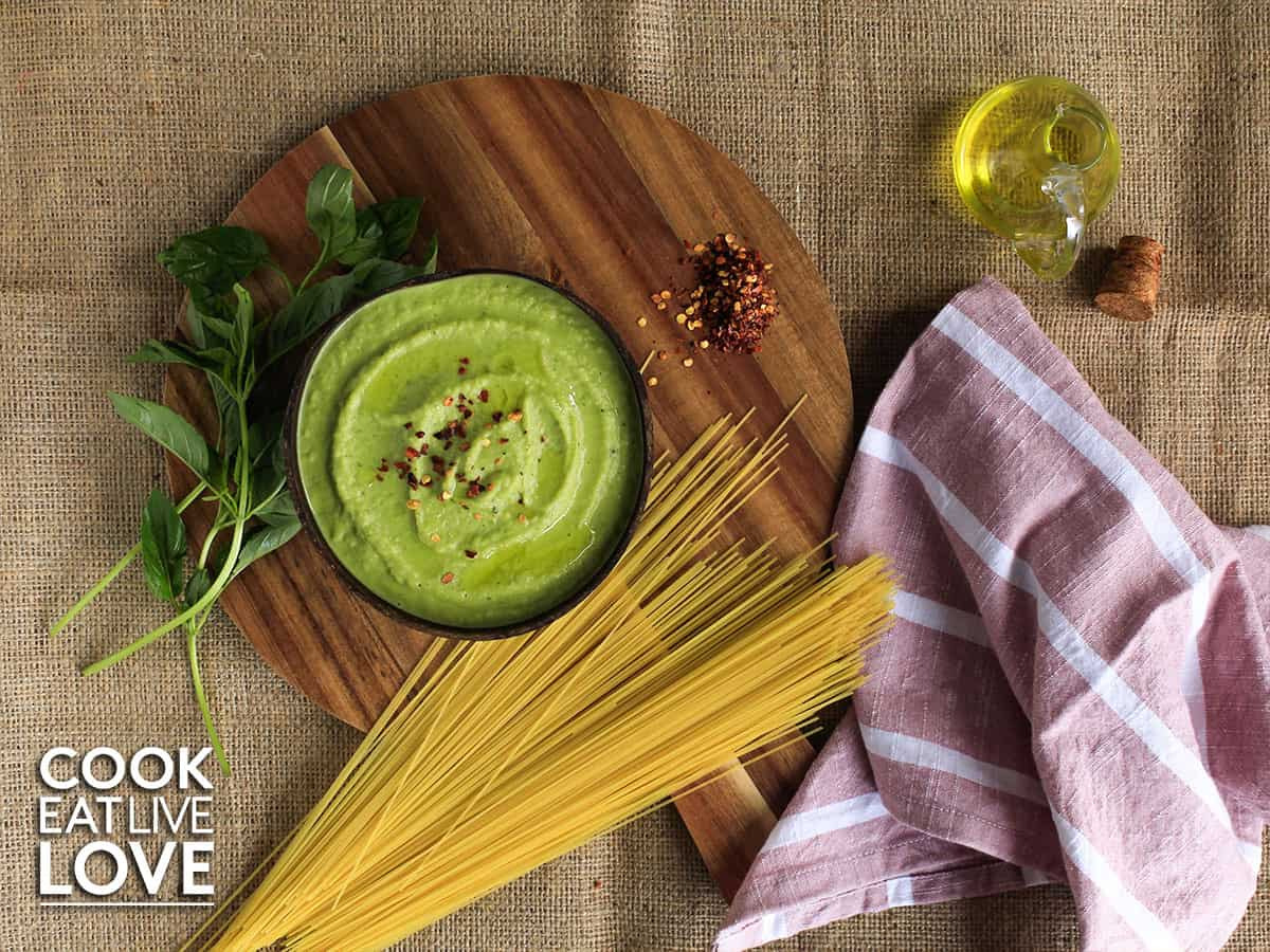 Overhead view of vegan alfredo sauce with pesto in bowl on round cutting board with dried pasta and basil.
