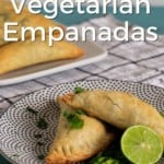 Pin for pinterest with close up of empanadas on plate garnished with lime and cilantro.