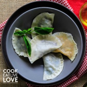 Overhead view of wonton raviolis served up in gray bowl garnished with fresh basil leaves.