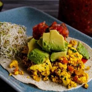 Delicious breakfast taco with tofu scramble inside tortilla with avocado and pico de gallo.