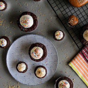 Overhead view of cupcakes on gray and white polka dot plate with cupcakes and sprinkles around it.
