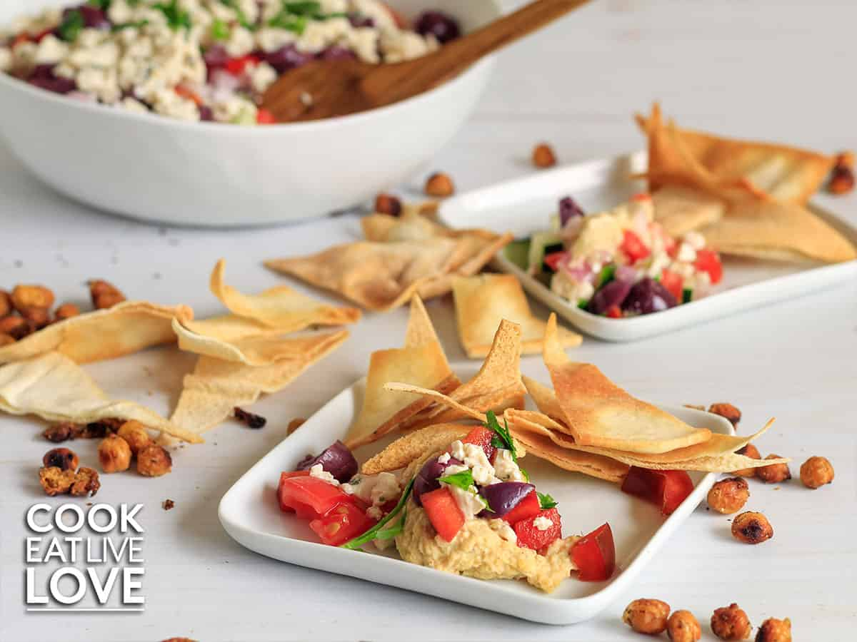 Easy vegan dip with mediterranean flavors served up on small white plates with pita chips.