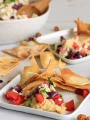 Plate of mediterranean dip served up on little square plates with bowl in background.