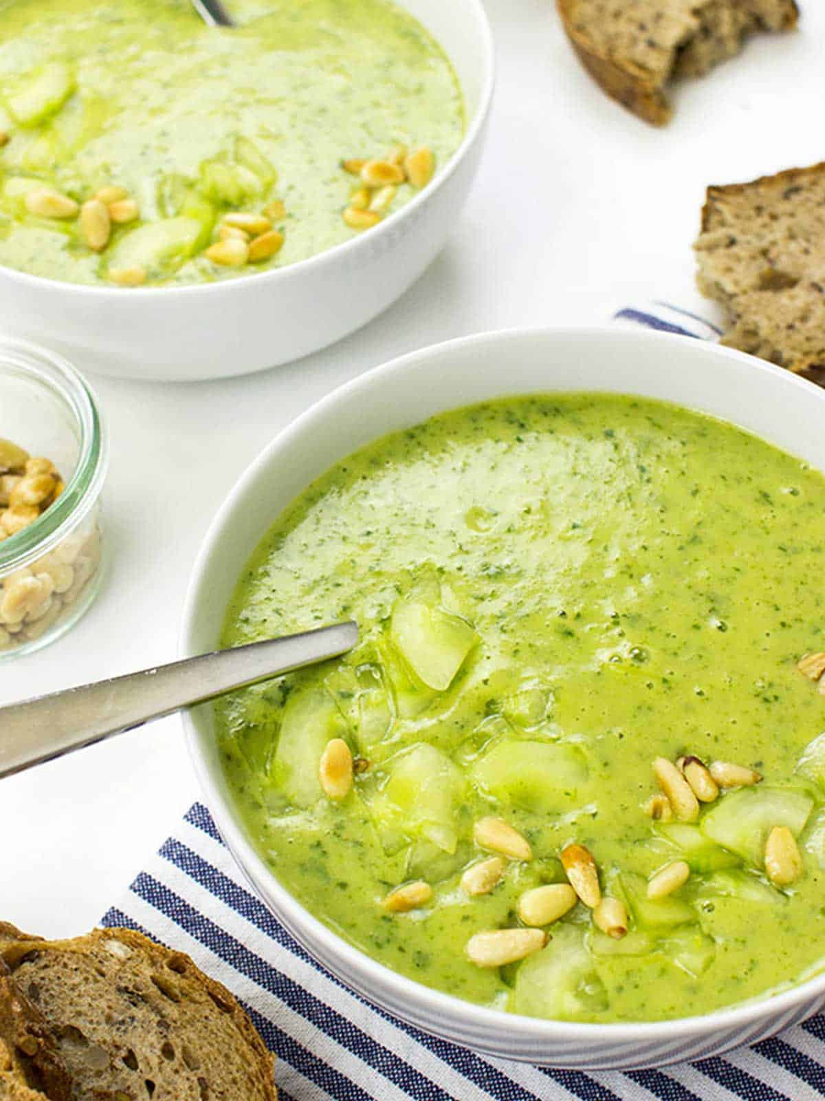 Vibrant green soup in white bowl with spoon and nuts on top.