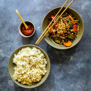Overhead view of bowl of rice and veggie stir fry with spicy red sauce.