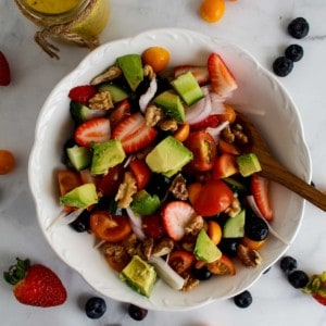 Overhead view of fruit salad with walnuts in white bowl.