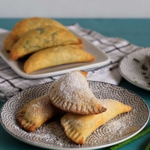 Corn and cheese empanadas on plate dusted with powdered sugar and other empanadas in the background.