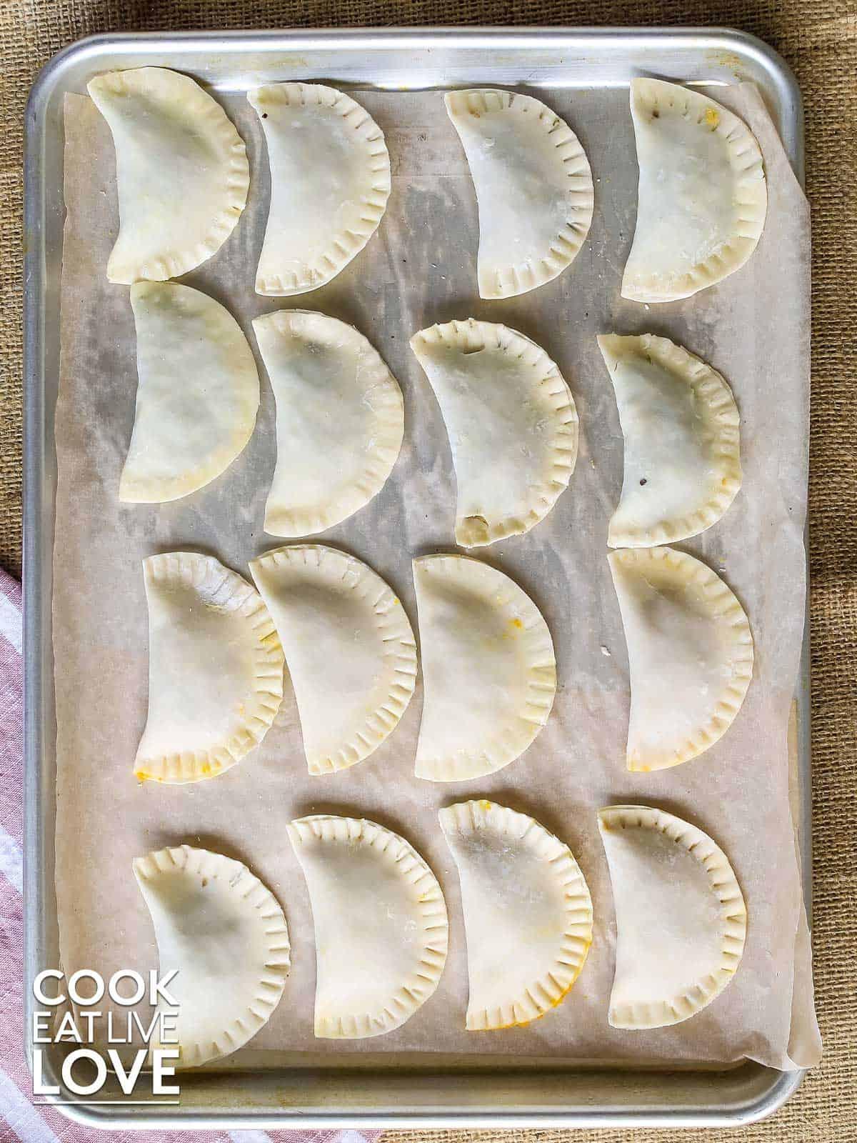 Wonton raviolis are laid out on baking sheet tray to freeze.